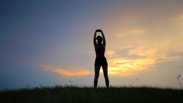 Zdravá žena v pozici lotus meditaci nad oranžové slunce