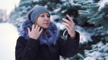 slow motion, the girl corrects make-up in the winter snow-covered park.