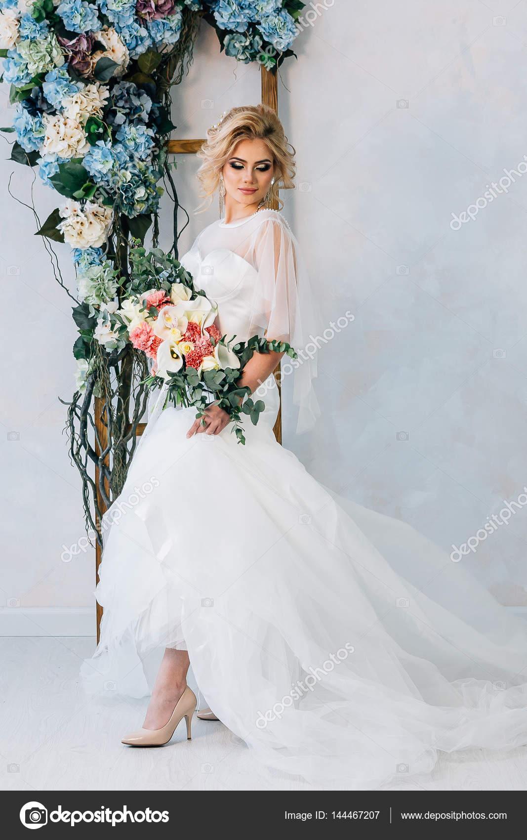Braut im Hochzeitskleid mit Blumenstrauß und Schuhe in den Händen ...