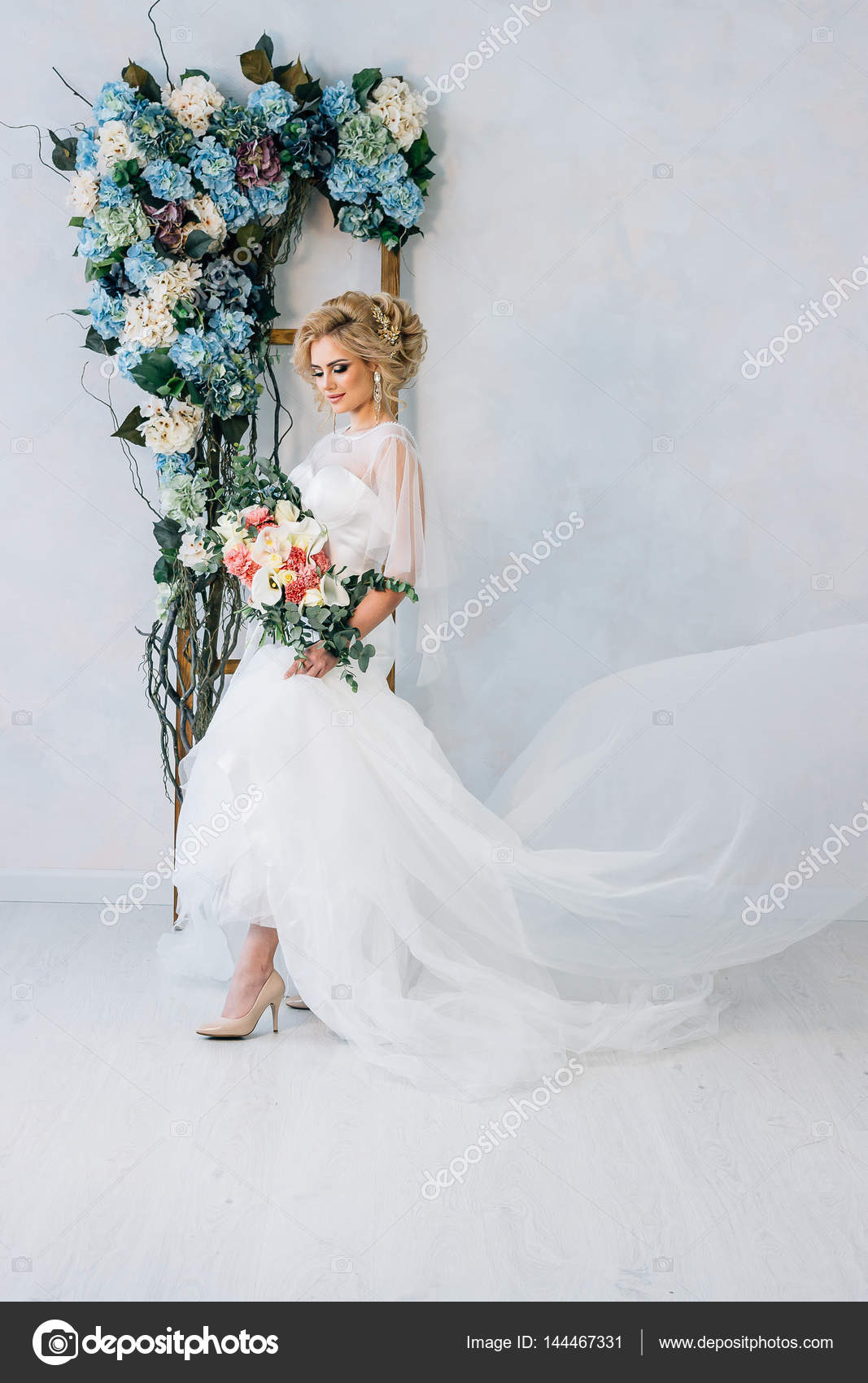 Beautiful bride in a wedding dress and shoes with bouquet in hand on ...