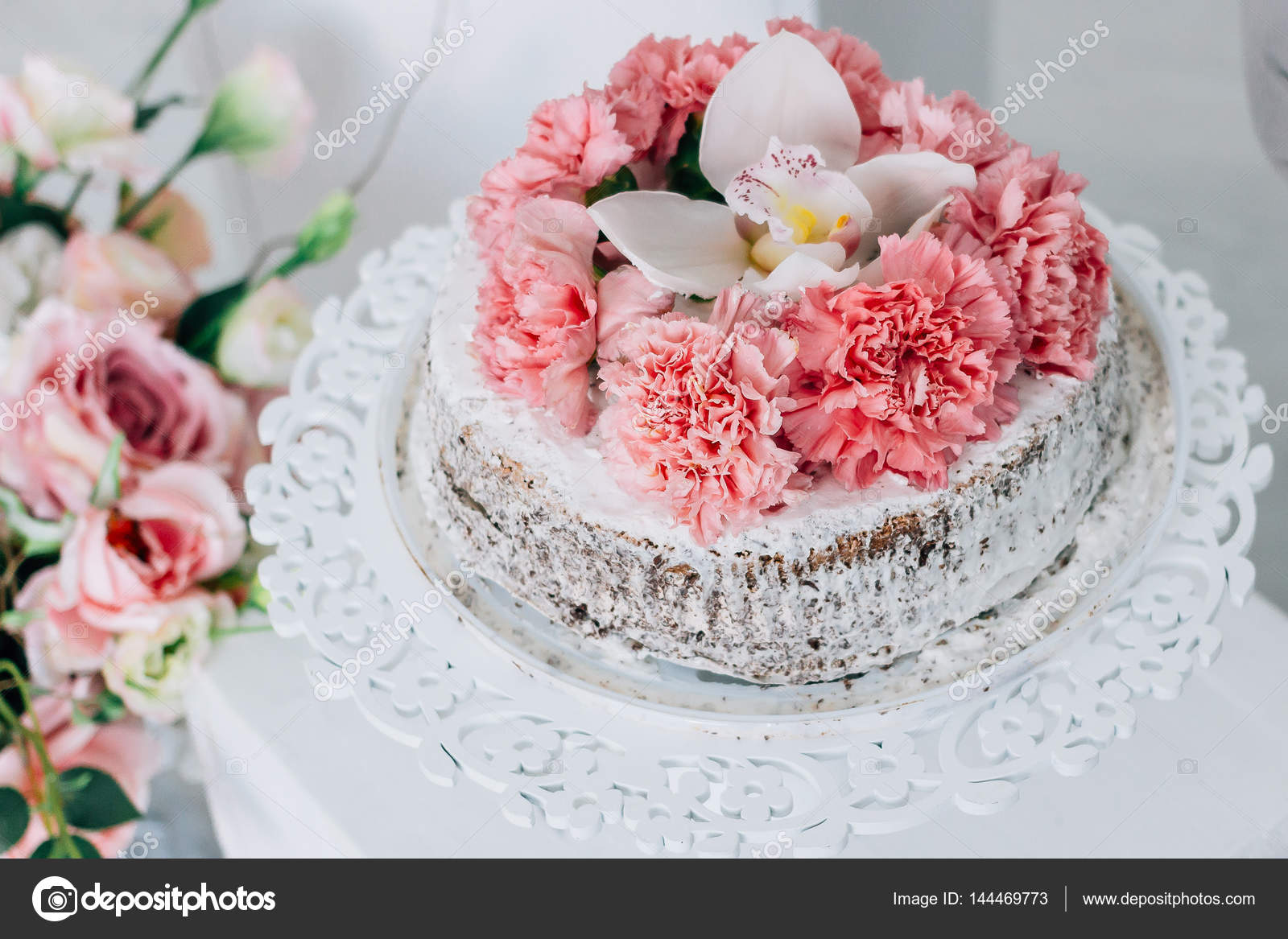 Wedding Cake On A White Pedestal Decorated With Fresh Flowers