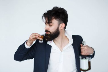 Drunk man with messy hair drinking whiskey