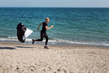 man running with training resistance parachute