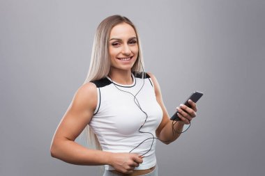 Young muscular woman with smartphone