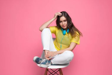 Brunette girl sitting in chair touching head
