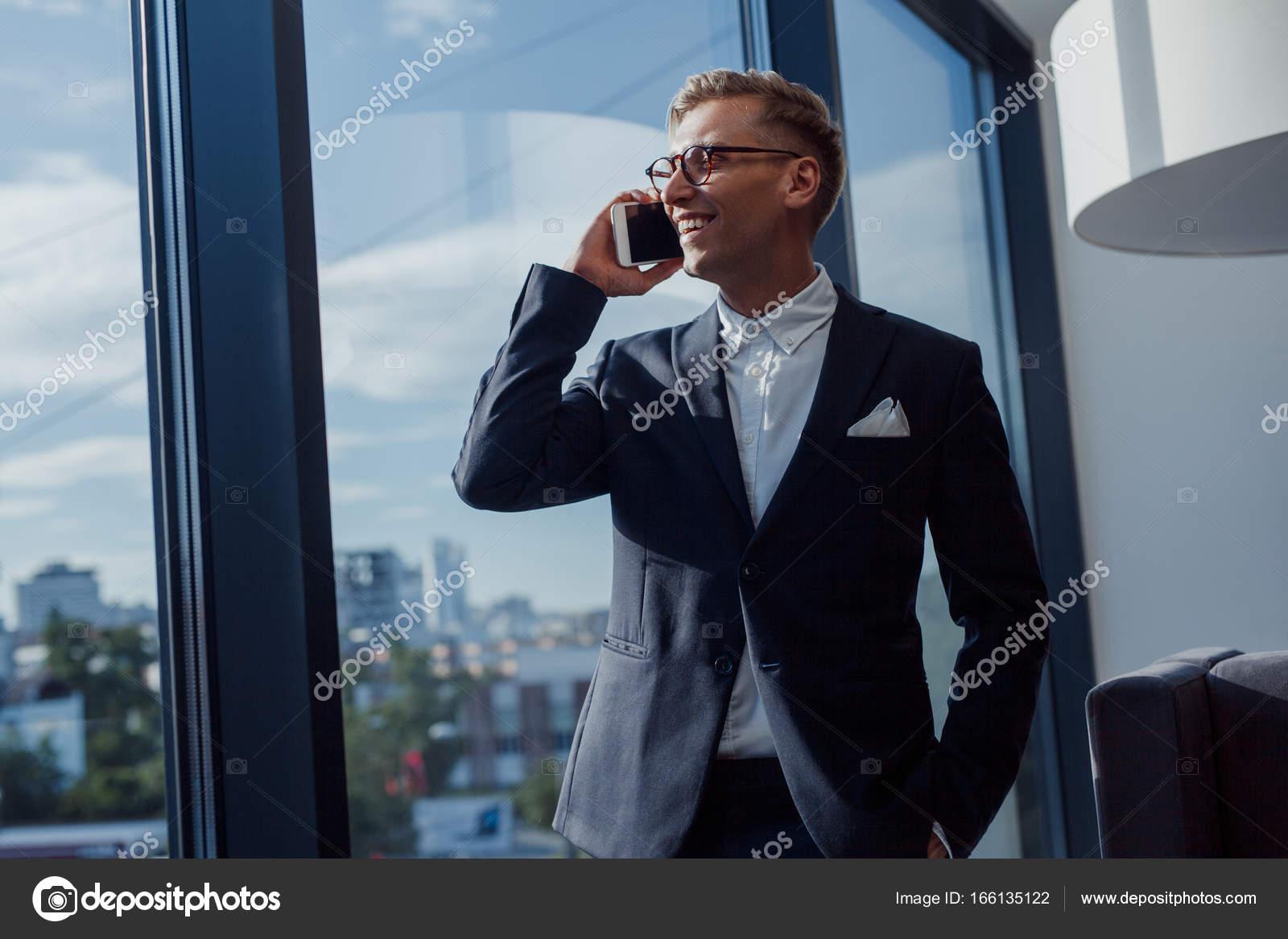 Vestito Elegante Ufficio : Elegante uomo d affari che parla sul telefono in ufficio u foto