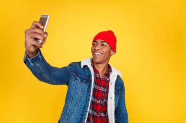 Trendy handsome man in red hat and denim using phone and taking selfie with smile on yellow backdrop. stock vector
