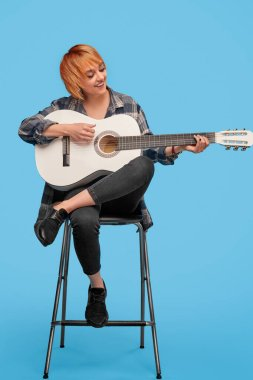 Cheerful woman playing guitar on chair
