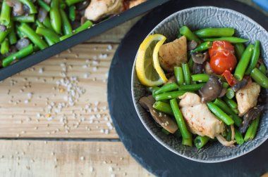 Top view of healthy hot salad with baked chicken breasts, green beans, cherry tomatoes, sliced mushrooms, lemon and sesame seeds served in a small bowl and round slate board on wooden table