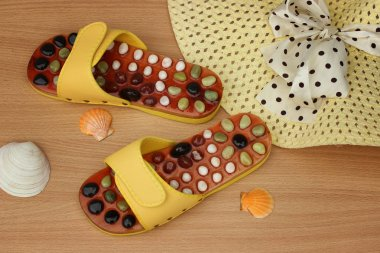 Set for the beach: yellow flip-flops and a straw hat with a bow and seashells close-up on a wooden background