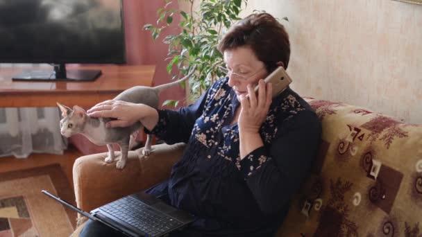vážně žena používající počítač a telefon
