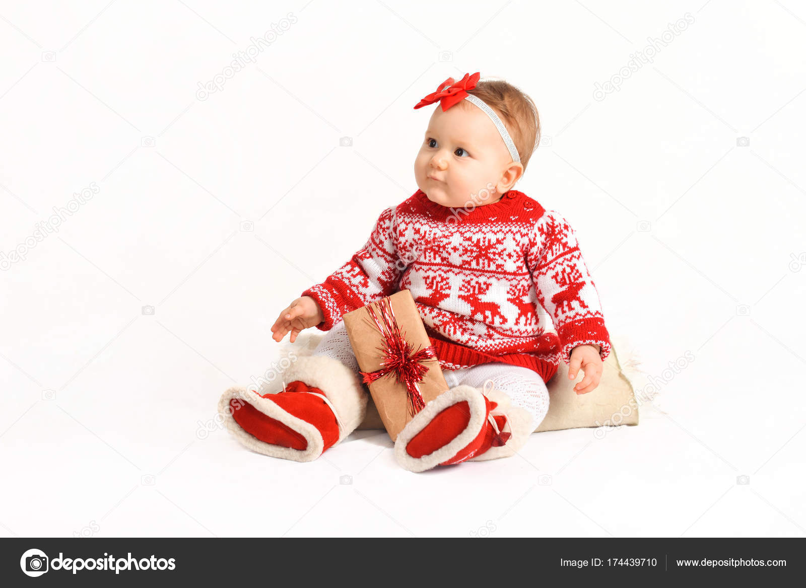 baby in a Christmas costume sits with gifts. beautiful New Years ...