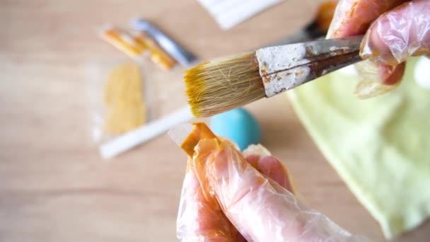 Bereiten Sie sich auf frohe Osterfeiertage vor. Die Hände des Meisters in transparenten Schutzhandschuhen zeigen das Ergebnis der Bemalung des Eiers in gelbgoldener Farbe. Nahaufnahme von oben auf Holz Hintergrund.
