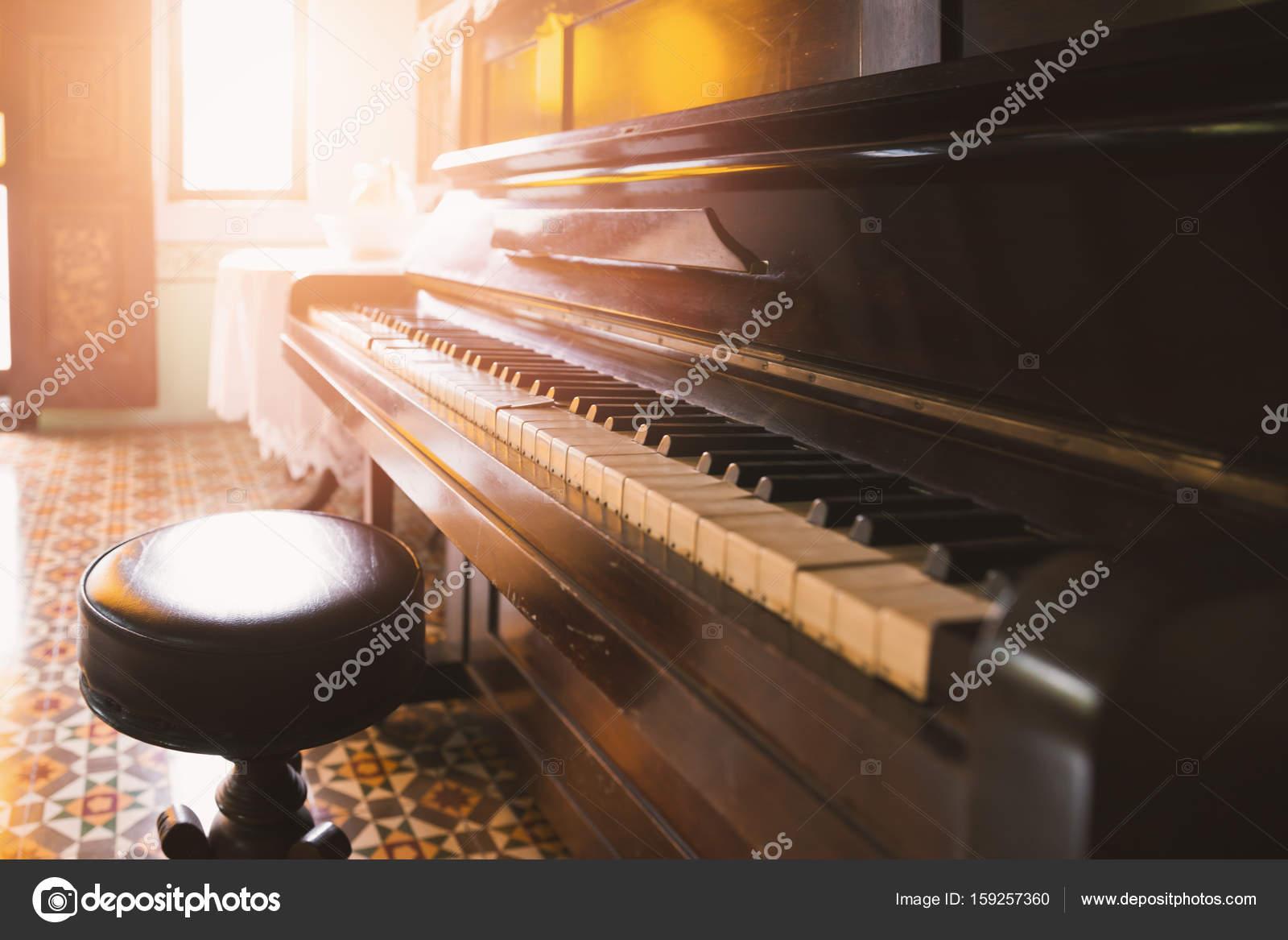 Vecchio e cracking pianoforte e sgabello con luce solare u foto