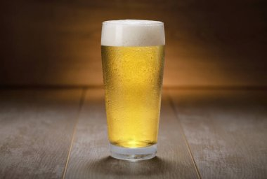 A colorful fresh pint glass of pale ale beer, pilsner, lager, traditional brew on wooden background