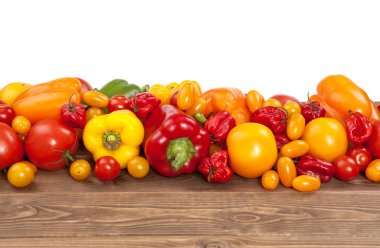 Colorful vegetables on white wooden background: tomatoes and paprika
