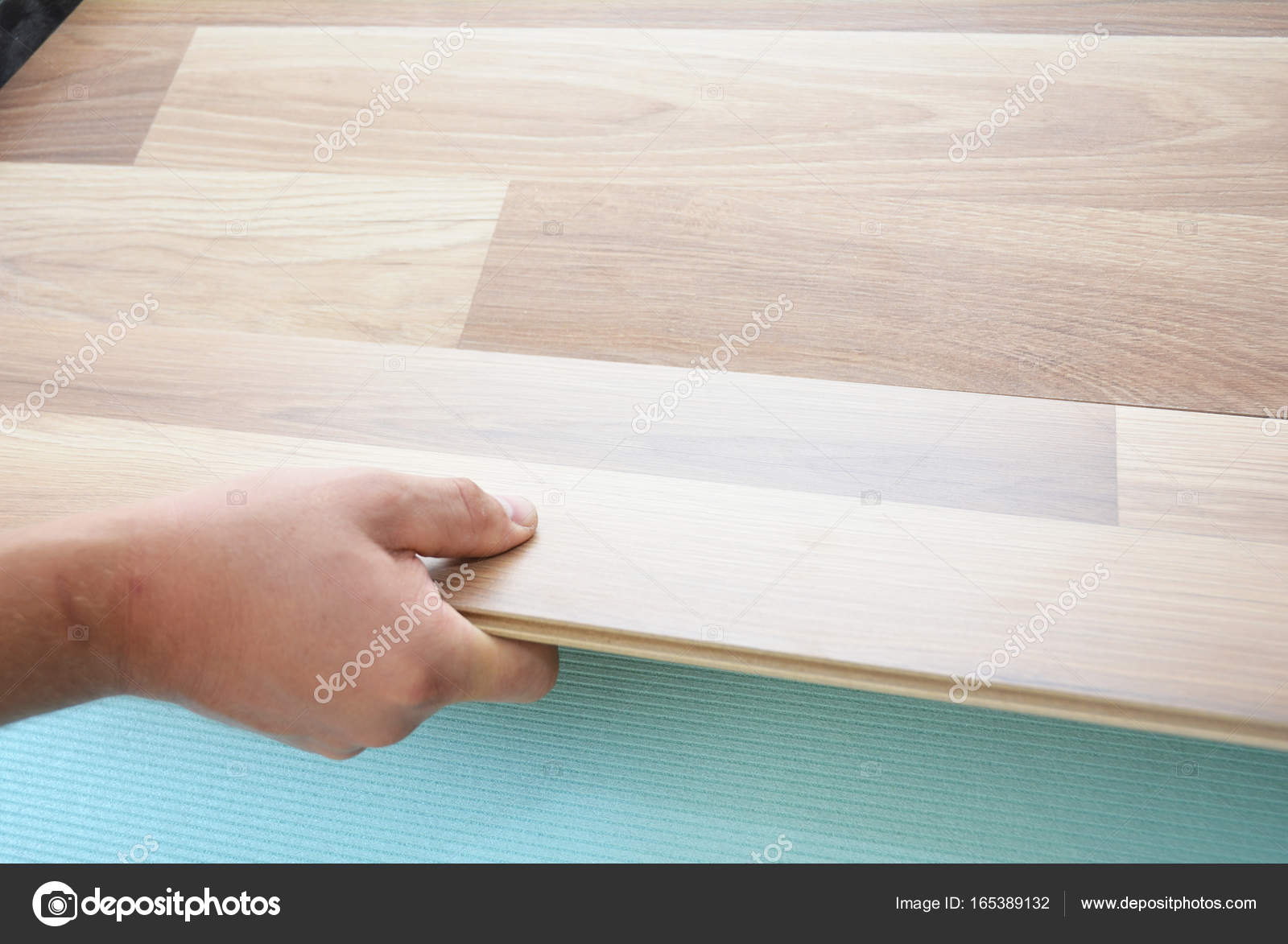 Contractor Installing Wooden Laminate Flooring With Insulation And Soundproofing Sheets Man Laying