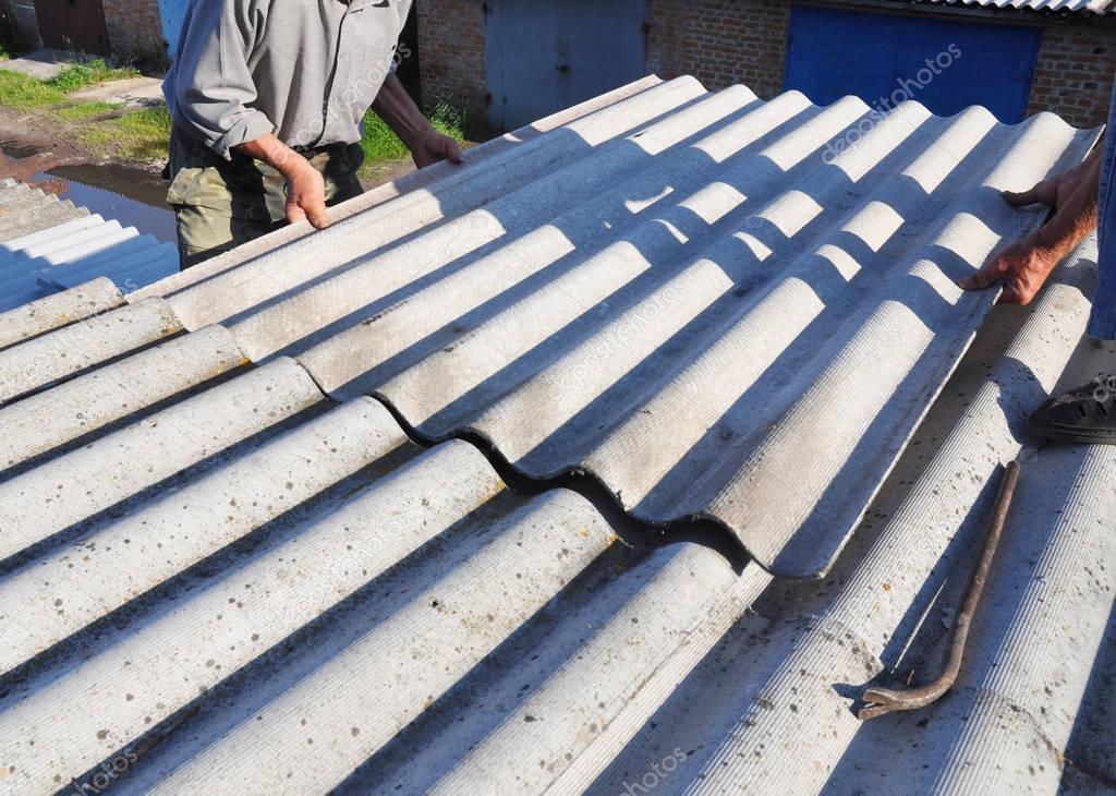 Enlèvement de l'amiante. Réparation de toiture amiante maison avec les mains de couvreur ...