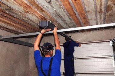 Contractors installing garage door opener.