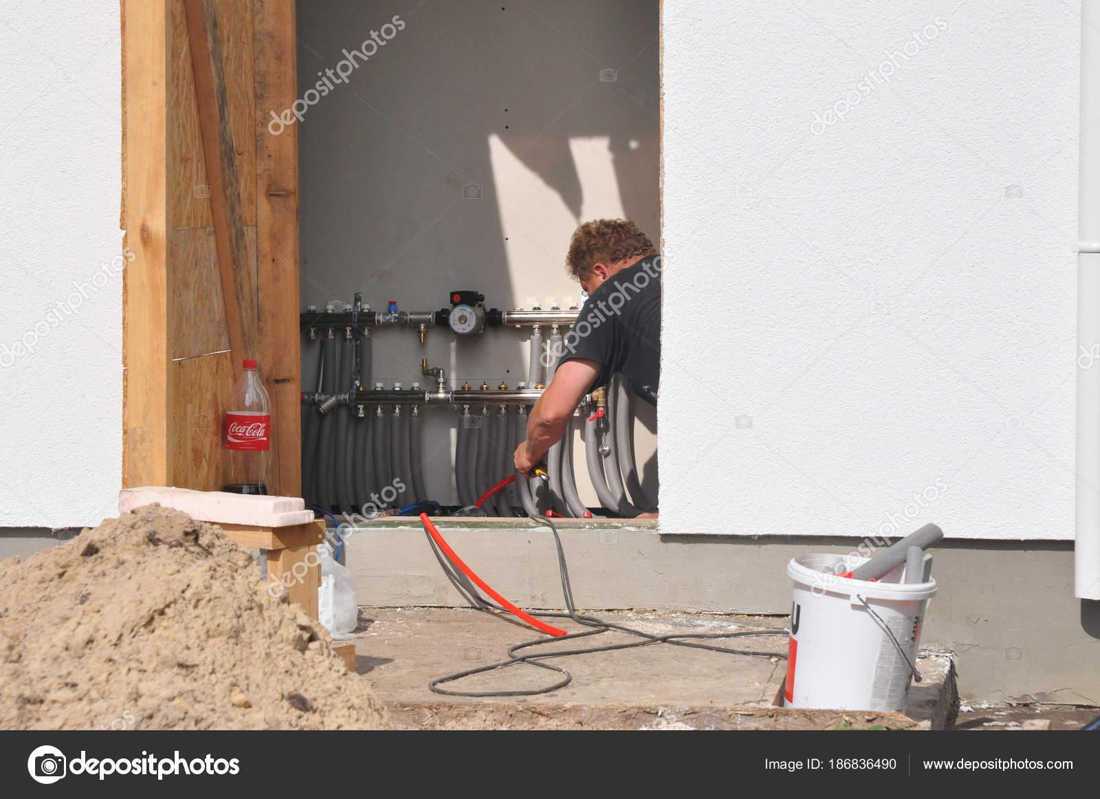 Man install underfloor water heating floor construction. Radiant ...