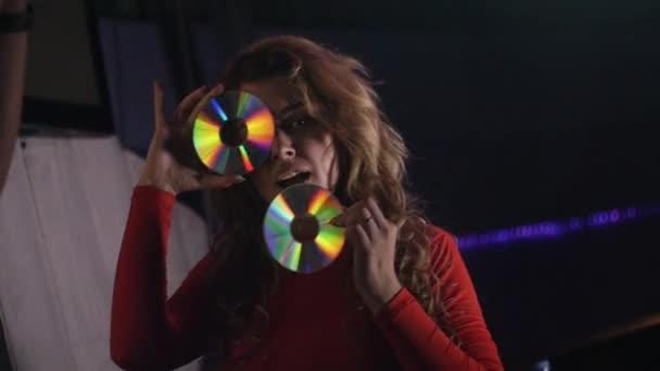 DJ dívka v červených šatech vlna Cd disku na tvář v nočním klubu. Podívejte se na neveřejné. Tanec