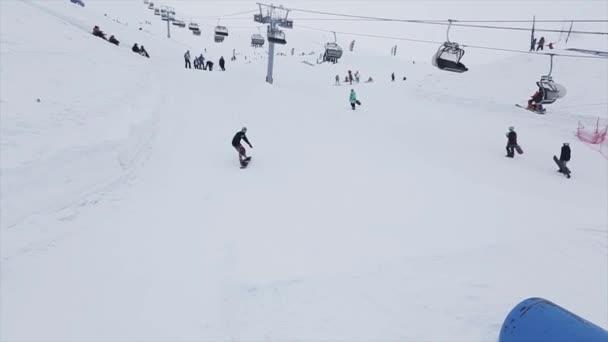 SOCHI, RUSSIA - MARCH 29, 2016: Snowboarder in uniform ride on springboard at ski resort in mountains. Extreme stunt. Cameraman.