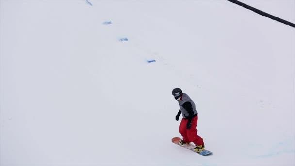 Sochi, Rusko - 29 března, 2016: Snowboardista helmu skok od odrazový můstek na lyžařské středisko. Zasněžené hory. Lyžaři. Lidé. Lyžařský vlek