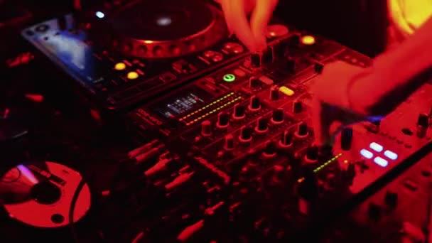 SAINT PETERSBURG, RUSSIA - AUGUST 27, 2011: Dj with headphones at turntable on party in nightclub. Red spotlights. Mc girl