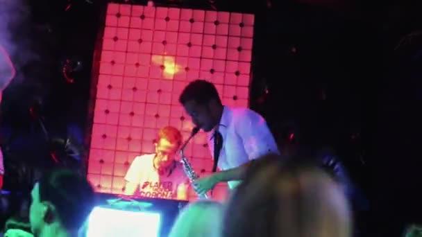 SAINT PETERSBURG, RUSSIA - AUGUST 27, 2011: Afroamerican man play on saxophone on party in nightclub. Mc girl. People. Dj
