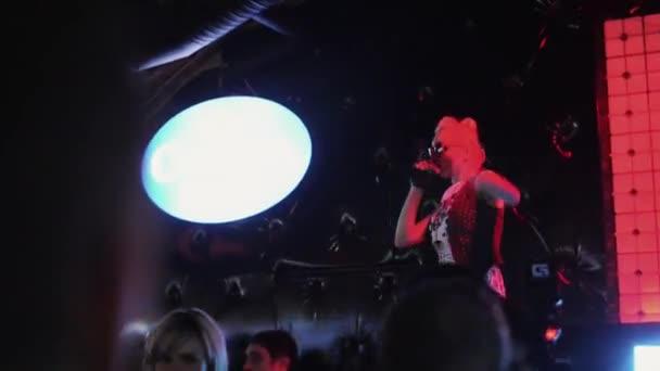 San Pietroburgo, Russia - 27 agosto 2011: Mc ragazza in occhiali da sole si esibiranno sul palco in discoteca. Faretti. Danza. Partito.