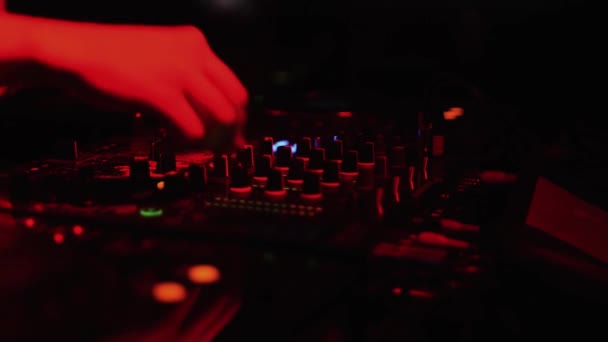 SAINT PETERSBURG, RUSSIA - AUGUST 27, 2011: Dj mixing at turntable on party in nightclub. Red spotlights. Flash. Music.