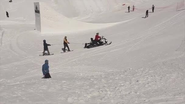 Soči, Rusko - 1. dubna 2016: Snowboardisty jezdit na skútru na lyžařské středisko. Lyžaři. Lidé. Zasněžené hory