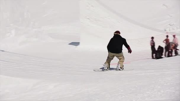 Sotschi, Russland - 1. April 2016: Snowboarder springen vom Sprungbrett mit vollem Salto, greifen sich das Brett in der Luft. Berglandschaft. blauer Himmel