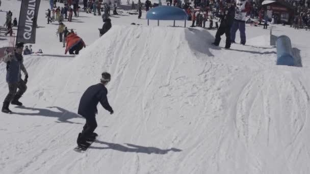 Snowboarder springen über Sprungbrett. Landschaft verschneiter Berge. Kameramann. sonniger Tag. Skilifte