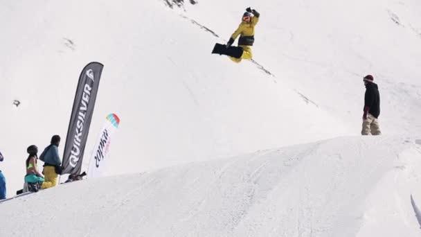 Sochi, Rusko - 1. dubna 2016: Snowboardista udělat skok do výšky z odrazový můstek, ohýbá nohy ve vzduchu, soustružení. Slunečno