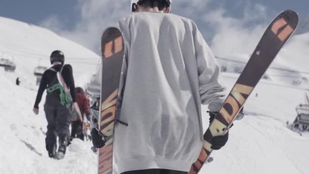 Zadní strana snowboardisty a lyžaře nahoru na svahu. Lyžařské středisko. Slunečný den. Lyžařské vleky. Sněhová Hora