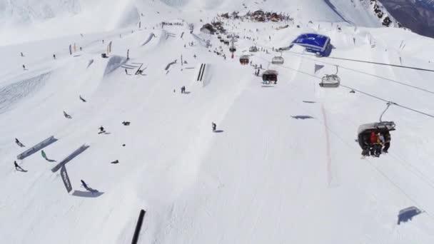 Soči, Rusko - 2. dubna 2016: Kvadrokoptéra natáčení snowboardisté, lyžaři na lyžařské letovisko. Lyžařské vleky. Skokanské můstky