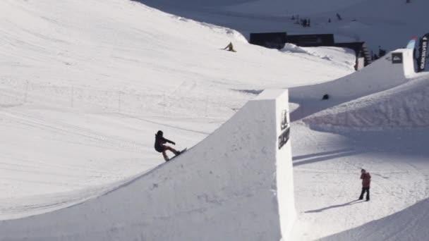 Sochi, Rusko - 2. dubna 2016: Snowboardista jízda na můstek. Otočte se ve vzduchu. Sunny. Lyžařské středisko. Extrémní