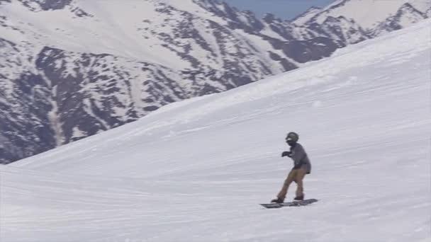 Sotschi, Russland - 2. April 2016: Snowboarderfahrt auf schneebedecktem Hang. Skigebiet. Berglandschaft. Aktiver Sport