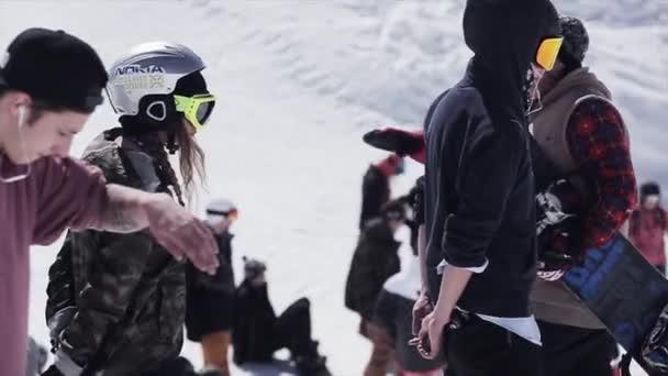 Sochi, Rusko - 2. dubna 2016: Lyžaře a snowboardisty na svahu. Slunečný den. Lyžařské středisko. Zasněžené hory