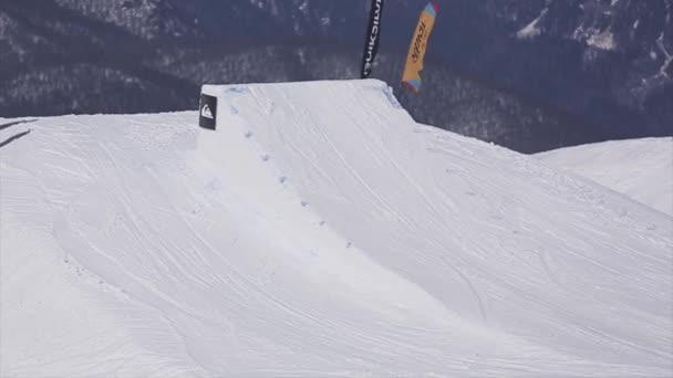 Sochi, Rusko - 2. dubna 2016: Lyžař skok z odrazový můstek, značka plná flip ve vzduchu. Scenérie pohoří. Sportovní