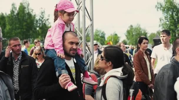 SAINT PETERSBURG, RUSSIA - SEPTEMBER 6, 2014: Little girl in pink cap sit on dad shoulder. Family. Summer festival. Sunny day.