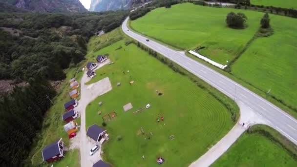 Skydiver parachuting achutung above mountains covered greenery. Landing on lawn.