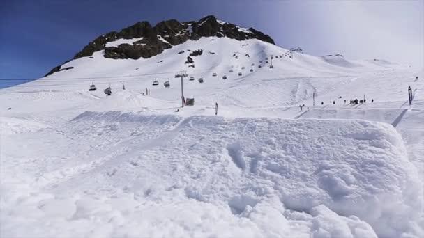 Sochi, Rusko - 1. dubna 2016: Snowboardista skok z odrazový můstek v přední fotoaparát, šnůry elektrické pro přístroje nohou. Přepínač na šířku. Slunečno