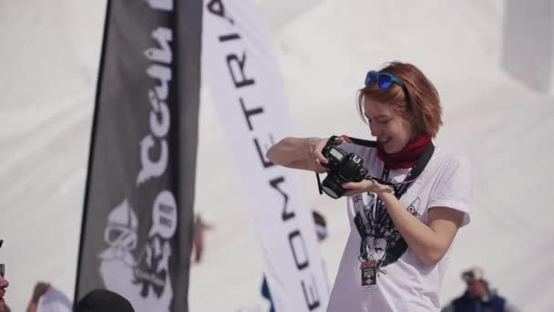 Sochi, Rusko - 1. dubna 2016: Lyžařské středisko. Dívka v bílé košili se profesionální fotografie. Encamp. Slunečný den