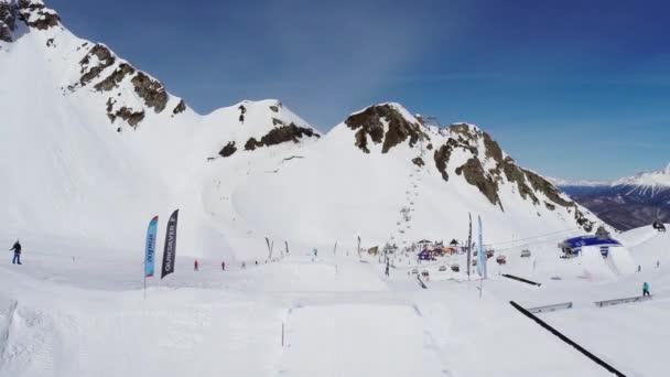 Soči, Rusko - duben 4, 2016: Quadrocopter natáčení snowboardisté skoky na můstek na lyžařské středisko. Krajina