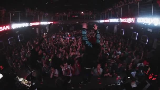 SOCHI, RUSSIA - APRIL 4, 2016: Man raise hands on bar stand and jump into crowd on party in nightclub. Fun. Entertainment