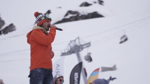 Sochi, Rusko - duben 4, 2016: Muž, řekněme v mikrofon v encamp. Snowboardisty a lyžaře. Lyžařské středisko. Hory