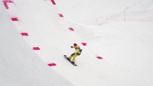 Sochi, Rusko - duben 4, 2016: Snowboardista jízdu na odrazový můstek, aby překlopit ve vzduchu. Lyžařské středisko. Žluté barvy
