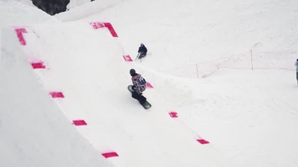 Sochi, Rusko - duben 4, 2016: Snowboardista skok do výšky z odrazový můstek, aby extrémní fanda. Výška. Hory